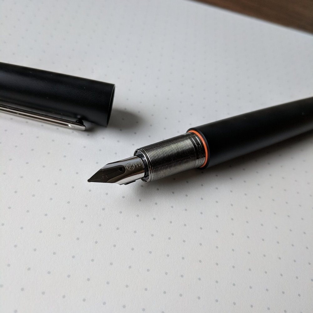 There is a fairly significant step-down from the barrel of the pen to the grip section, which isn't sharp, but I can still feel it when writing. Note the orange highlight, which adds a pop of color and stands out nicely on the otherwise dark design.