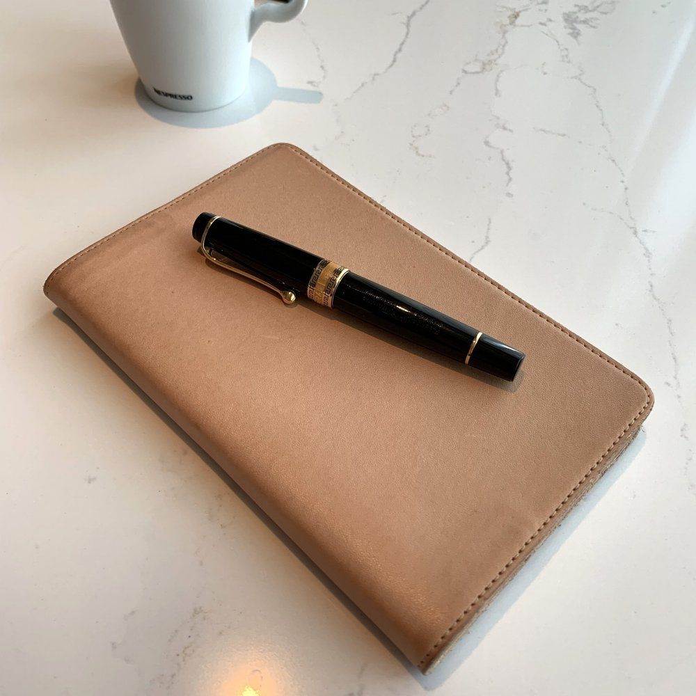 "My ""go-anywhere"" rollerball pen: the Aurora Optima, shown here on top of my  Nanami Paper Cafe Note B6  in  Gfeller natural leather cover , which is starting to show some wear!"
