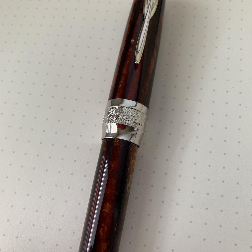Here you can see the striations in the acrylic. Lovers of vintage Arco celluloid will say it's not the same - and it's not - but the material is beautiful in its own right. The cap features a twist magnetic closure, with a metal piston knob that allows you to post the pen using the magnet in the cap.