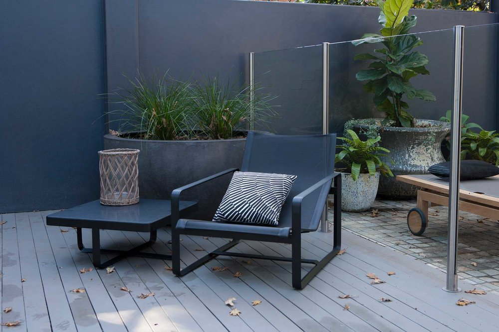 A sexy and sleek black, poolside accent chair from our Pymble Landscape Design Project