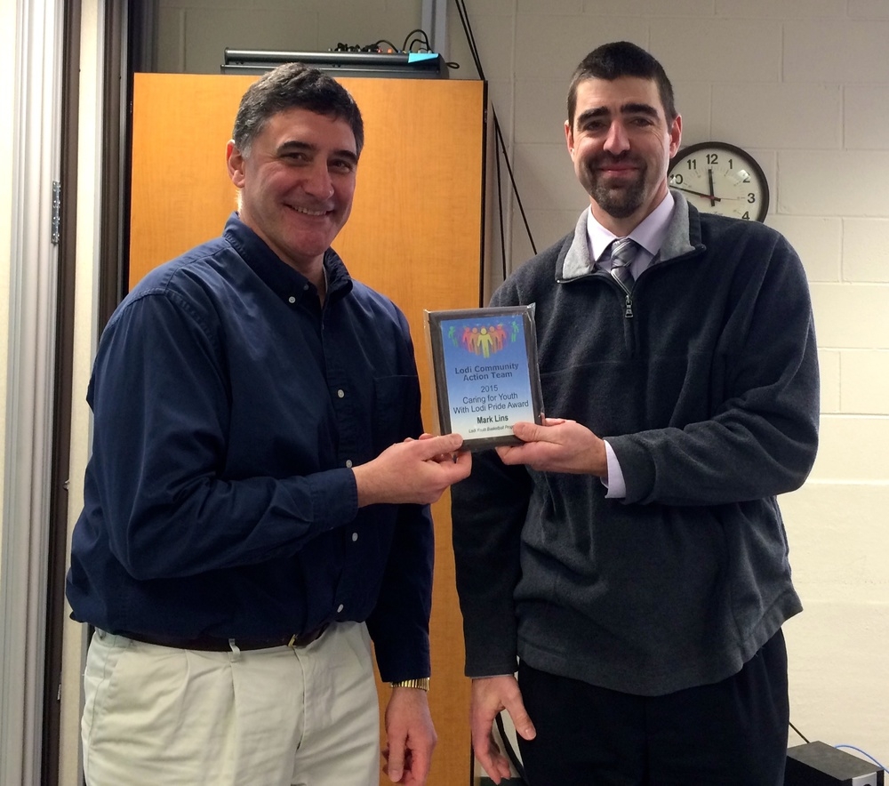 Vince Breunig (right), Lodi High School Principal, proudly presents a Lodi Pride Award to Mark Lins (left), Coach of the Lodi Youth Basketball Program.