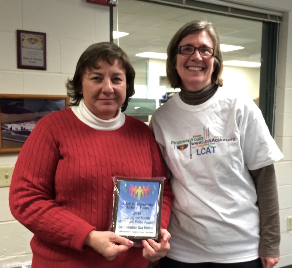 Paula Enger (right), LCAT Project Coordinator, presents a Lodi Pride Award to Jenny Anderson (left), Manager of the Lodi Marathon #303 gas station.