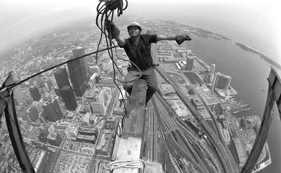 """Perched 440 meters above Toronto and 9 meters out from the growing CN Tower iron worker Larry Porter pulls at the hook of giant crane as he installs the outriggers that will be used to lift the restaurant."" -  Toronto Star"