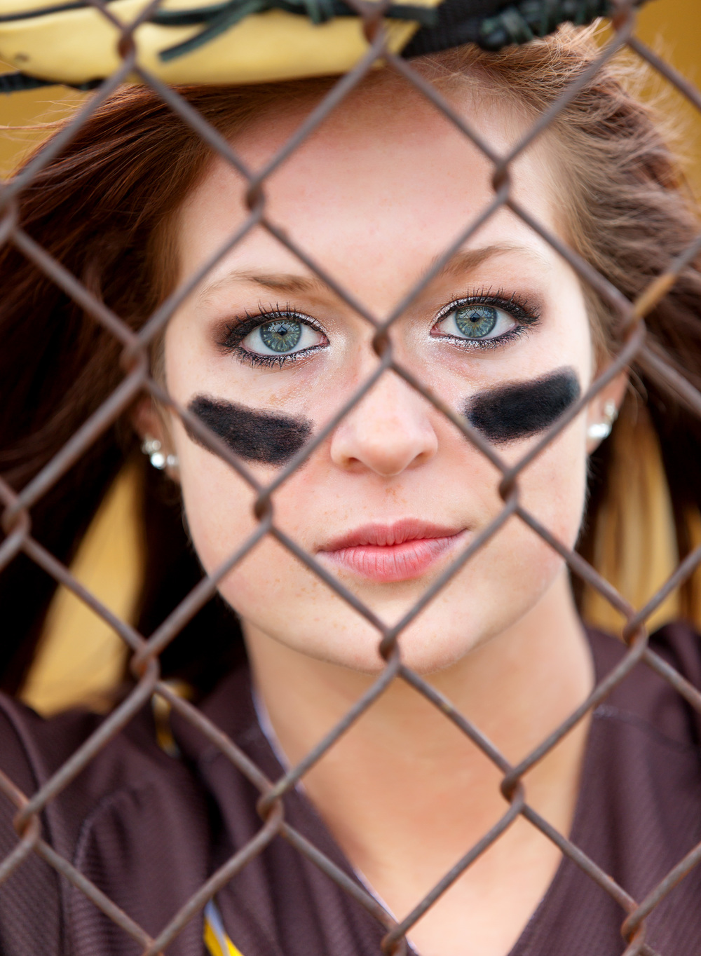 blonde senior girl softball player with blue eyes and eye black behind a chain link fence in Apple Creek, Ohio