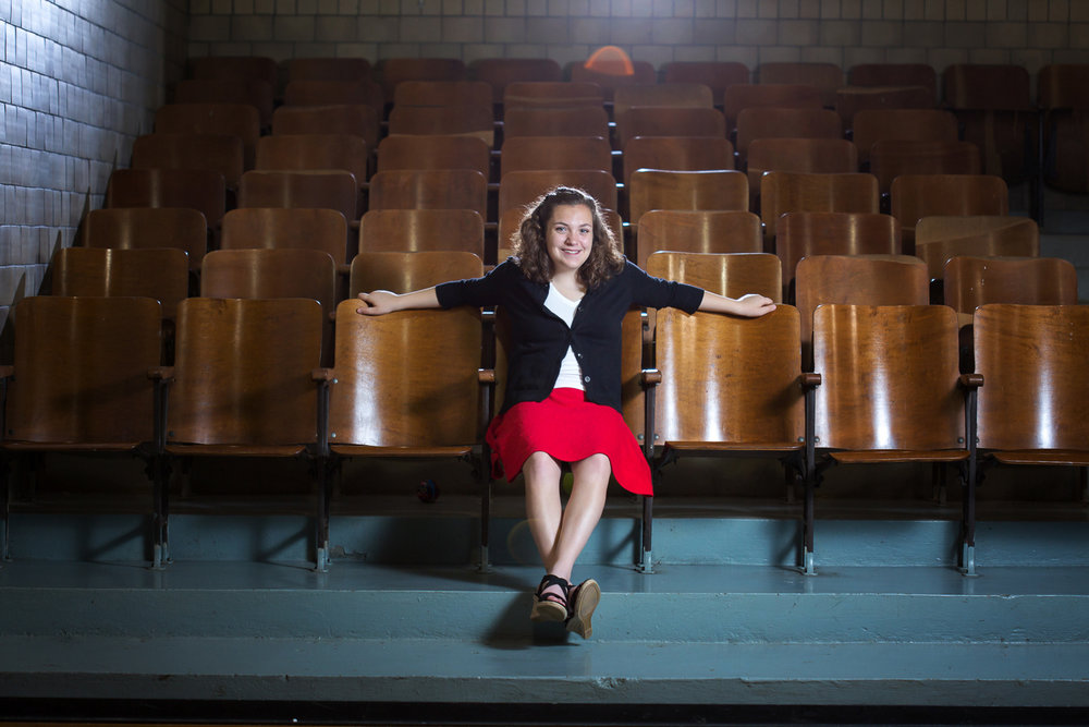 brunette senior girl wearing a vintage 1950s white top black sweater and red skirt sitting in an old school auditorium with brown fold-down seats like she is about to watch an old film in Wooster Ohio