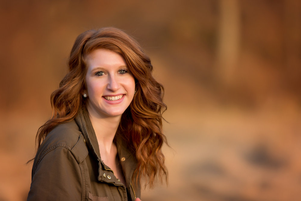 red-head senior girl with green jacket with blurry fall color scene behind her in Fredericksburg Ohio