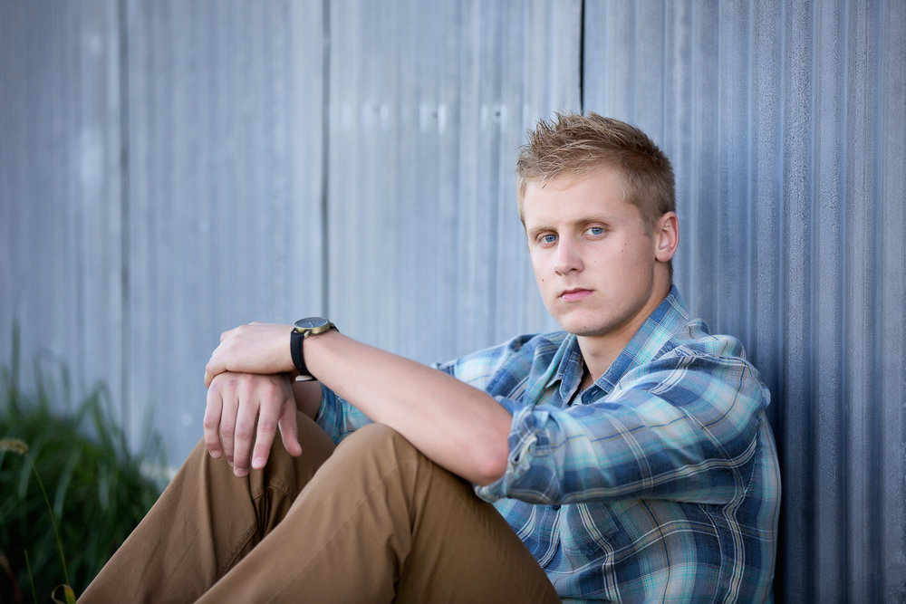 blonde senior guy wearing a blue plaid shirt and khaki pants sitting against grungy blue corrigated metal siding in Orrville Ohio