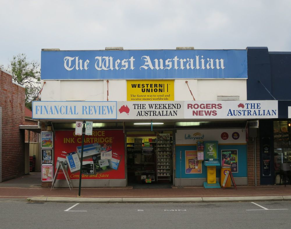 A typical West Australian newsagency. 7 pieces of third-party signage and Rogers News.