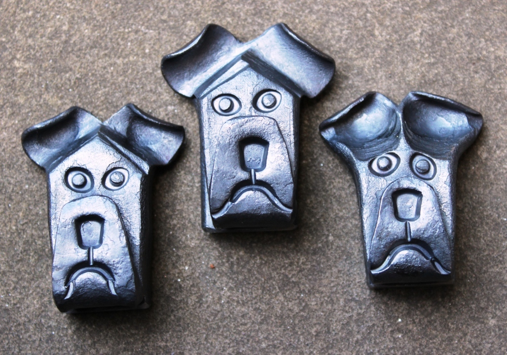 Forged dog head paperweights by Mick Maxen