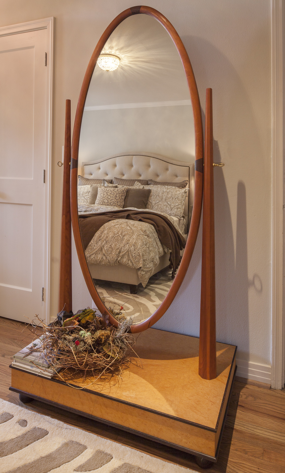 Cheval mirror of multiple woods: Base of birds-eye maple; base trim of African wenge; vertical supports of cherry and oval mirror also trimmed with cherry and an inlay of wenge. Design adapted by Michael Reznikoff/RCF.