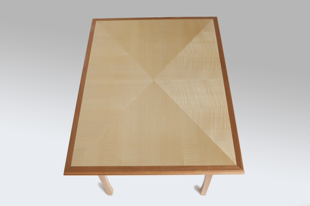 "Coffee table of quarter figured sycamore, laid-up in the ""reverse diamond"" pattern with cherrywood edge, trim and base. Of note is how the reverse diamond pattern changes contrast with its angle to the light.  Dimensions: 33"" x 25"" x 20"" high  Design by Reznikoff Custom Furniture"