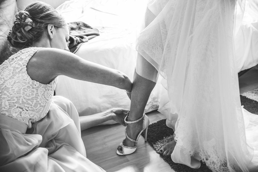 Bridesmaid fastening bride's shoes black and white