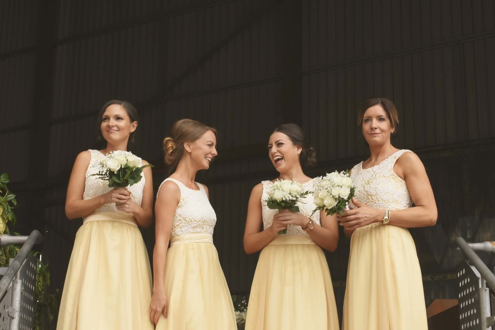 Bridesmaids laughing holding their bouquets