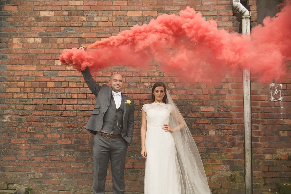 Bride and groom outside Victoria Warehouse with smoke