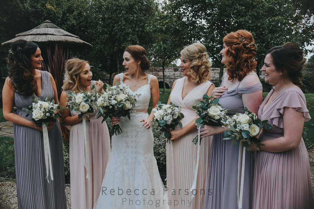 Bride in landscaped gardens with bridesmaids