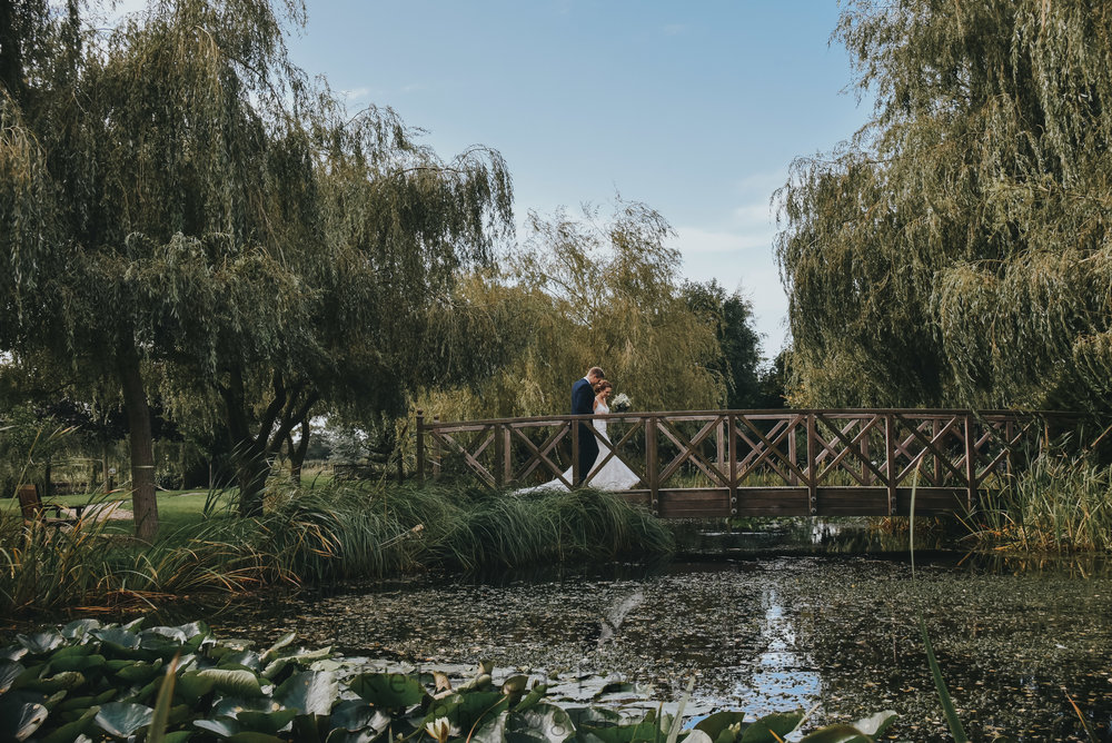 Bride and groom on bridge in sensory garden