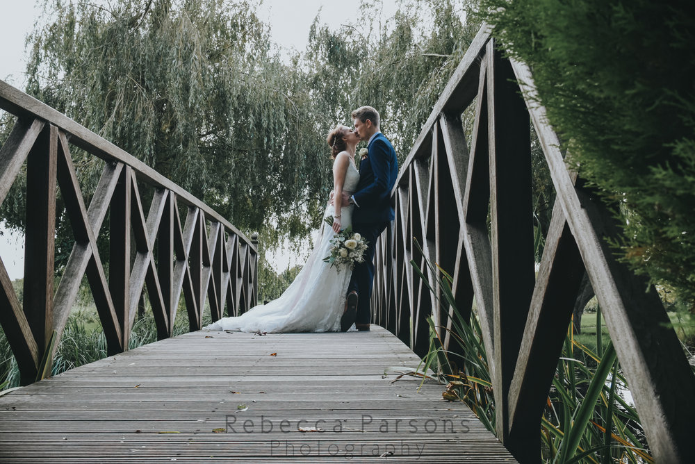 Bride and groom kissing on bridge in garden