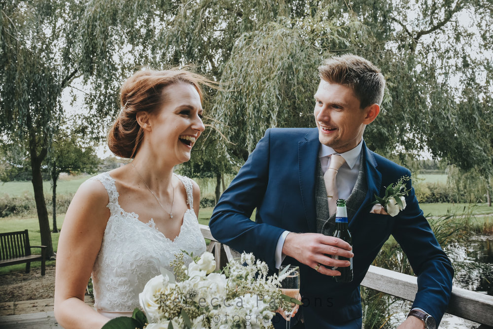 Bride and groom laughing in gardens