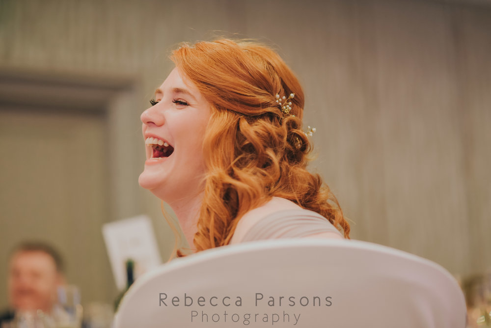 Bridesmaid laughing during speeches
