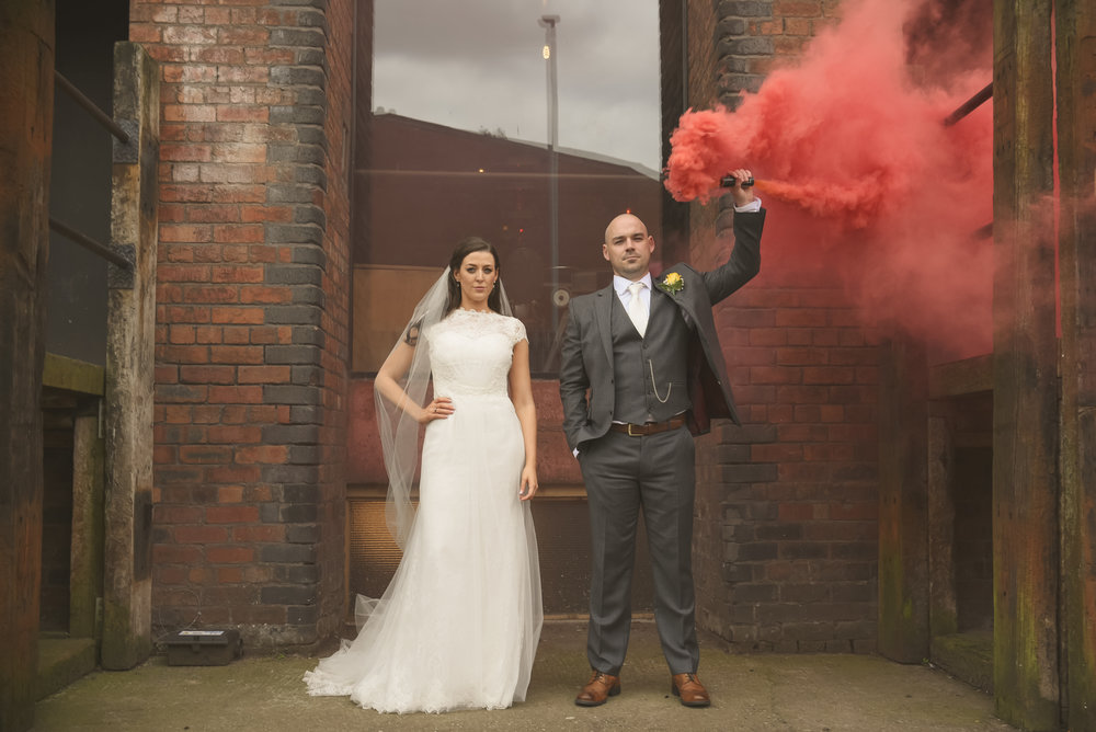Bride and groom outside Victoria Warehouse with red smoke