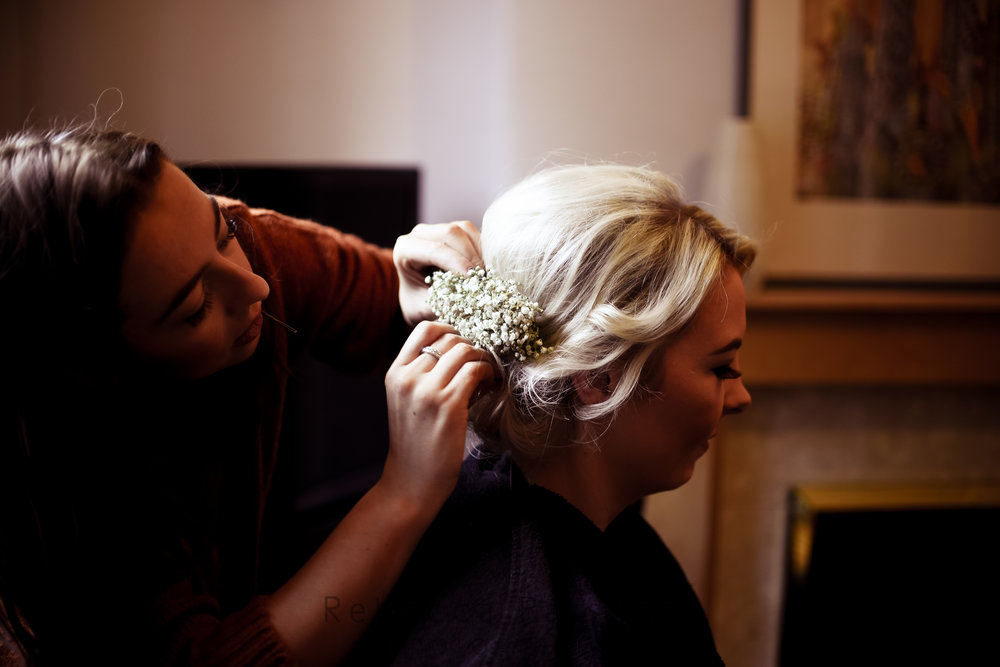 Bride hair being styled with flowers
