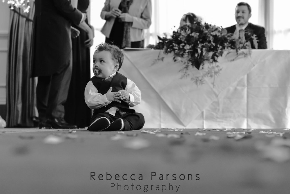 son of bride and groom sitting in front of a table black and white