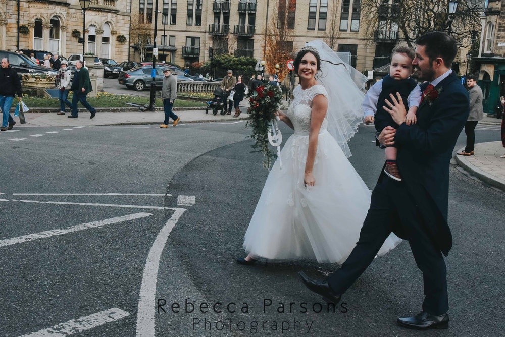 bride and groom crossing road with son