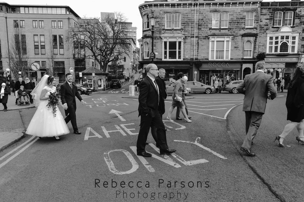 wedding guests crossing road black and white