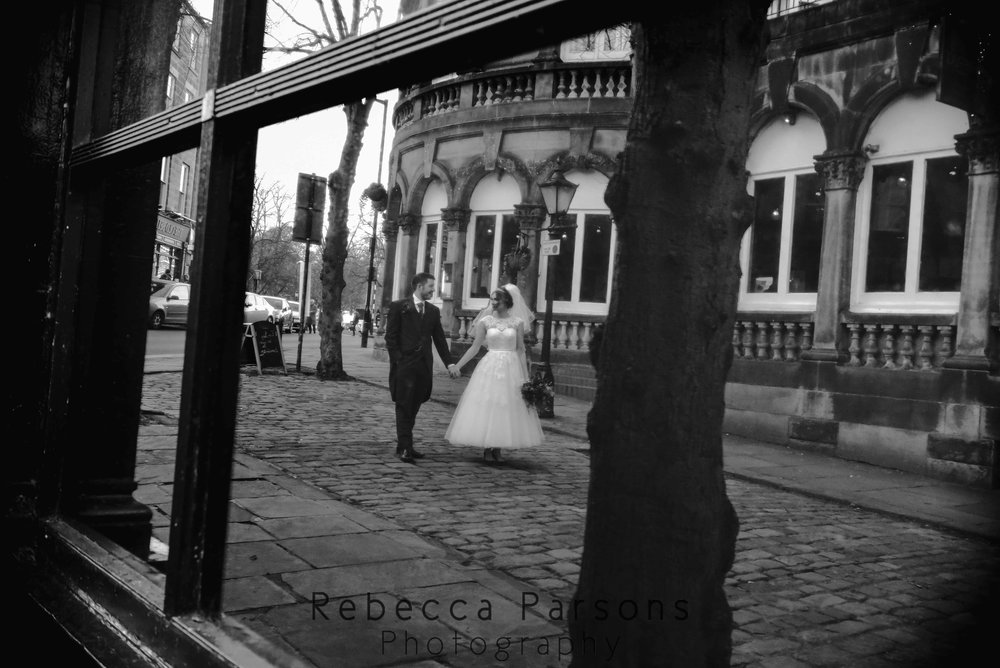 reflection of bride and groom in window black and white