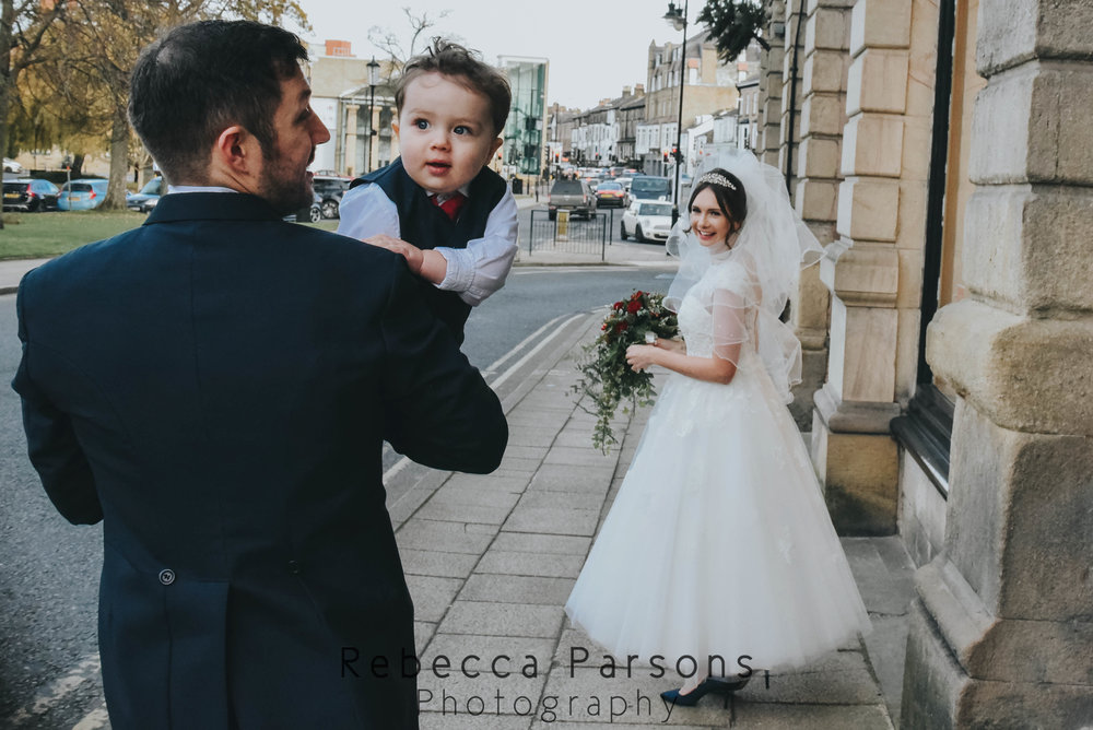 bride and groom and son walking down street
