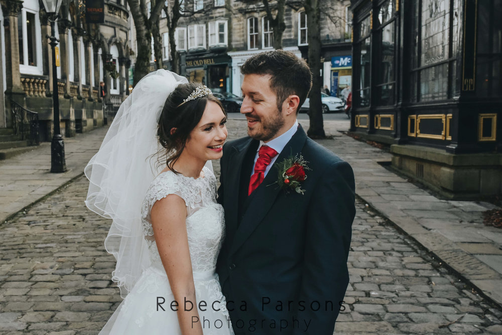 bride and groom smiling on cobbled street