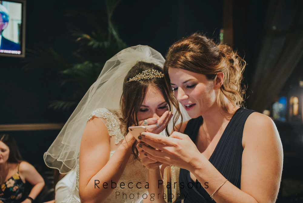 bride and friend looking at phone