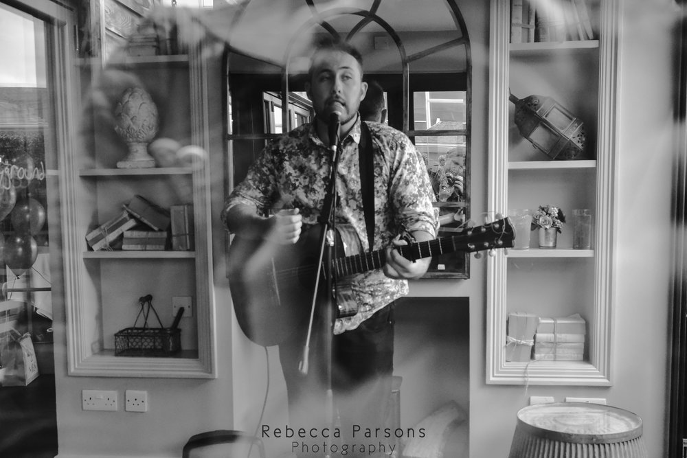 singer performing with guitar black and white
