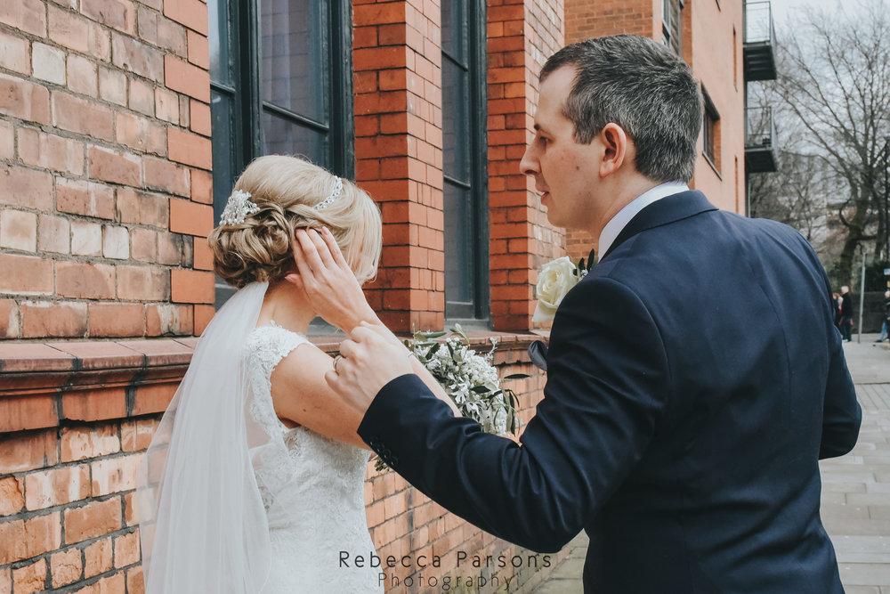 groom adjusting brides hair