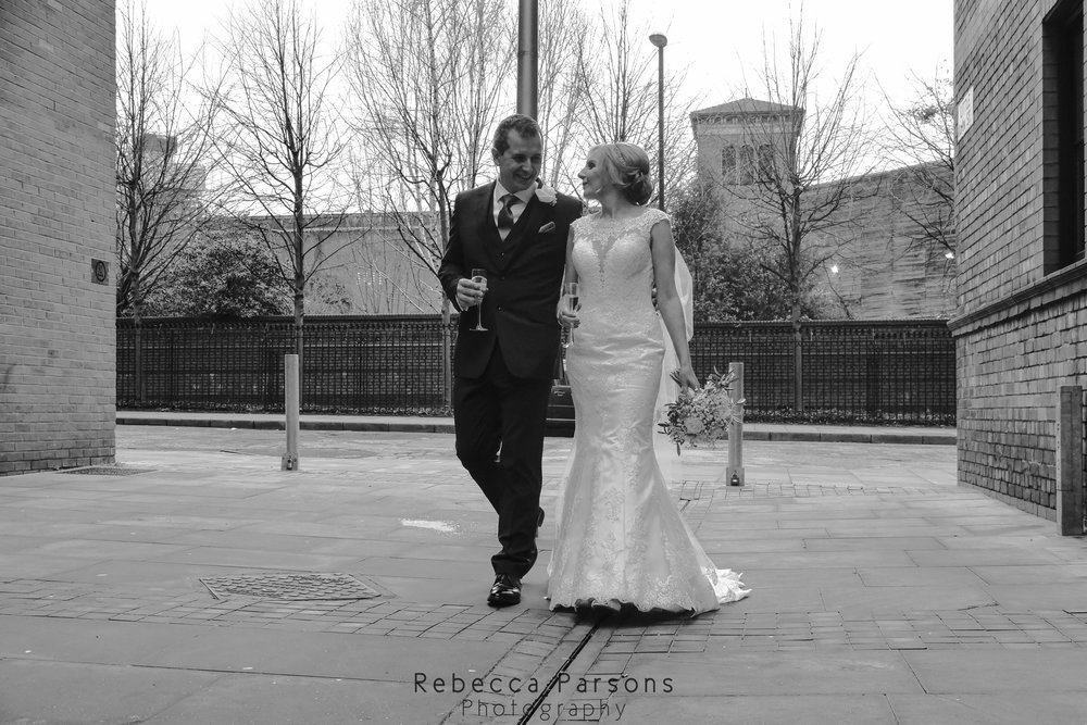 black and white bride and groom walking through Manchester