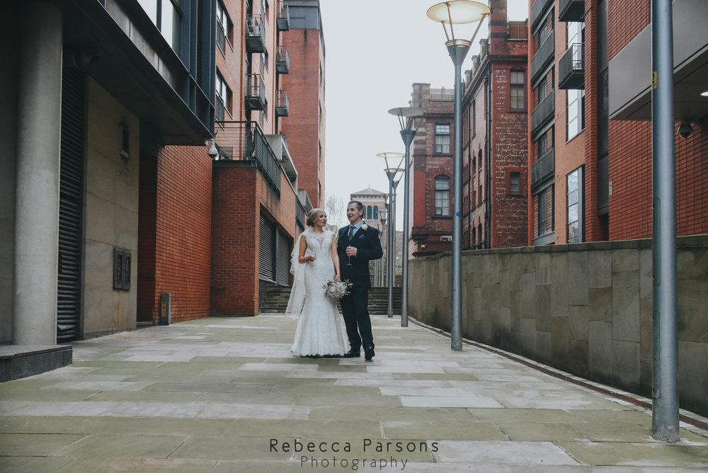 bride and groom walking between buildings in Manchester