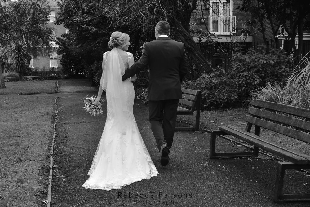 black and white behind bride and groom as they walked down street