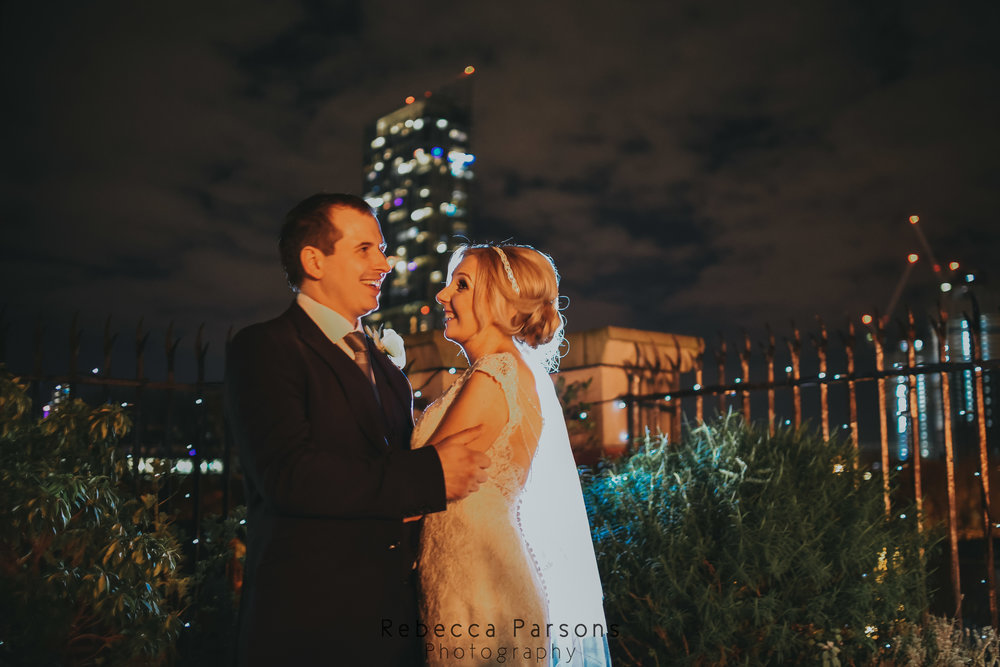 bride and groom outside Hilton hotel at night