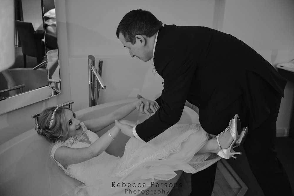 black and white groom helping bride out of bath