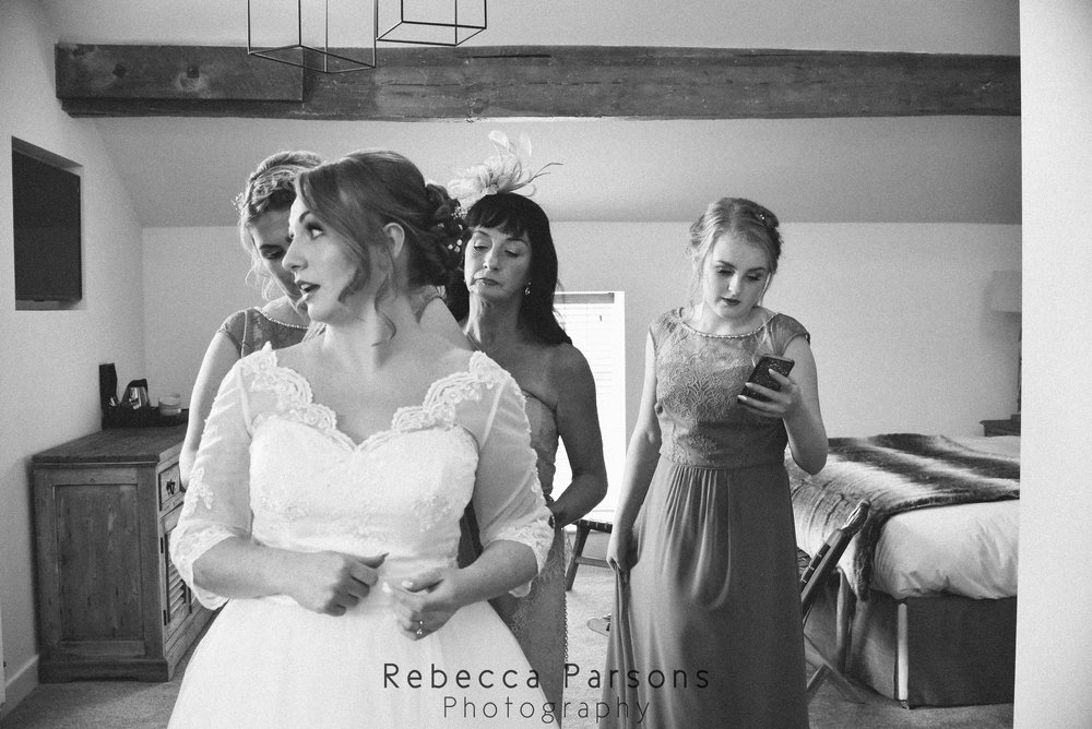 bride dress being fastened black and white