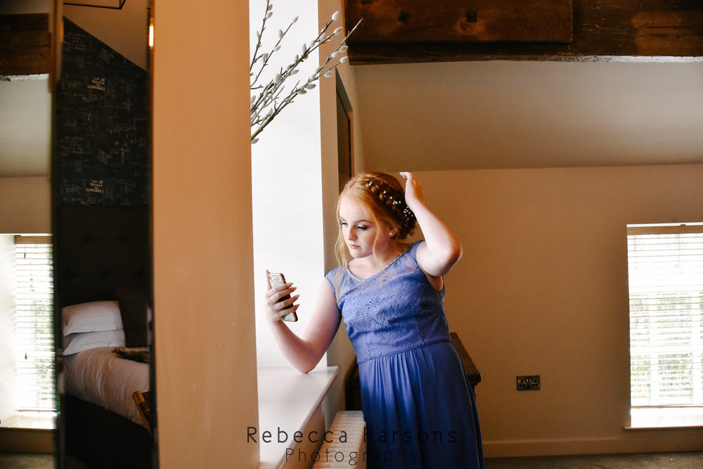 bridesmaid at window on mobile phone
