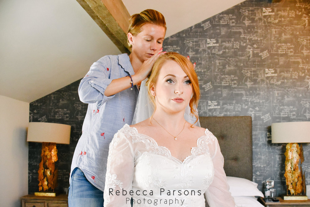 make up artist adjusting bridal veil