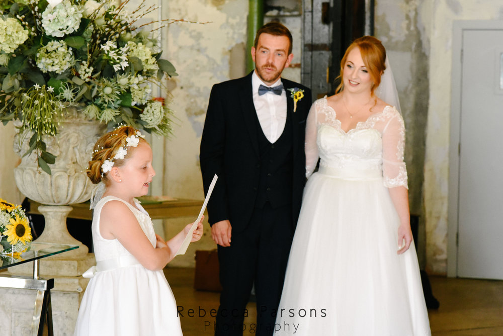 flower girl reading while bride and groom watch