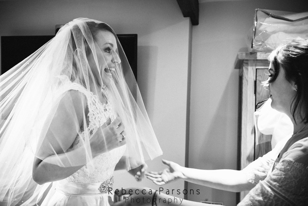 excited bride wit veil over face black and white