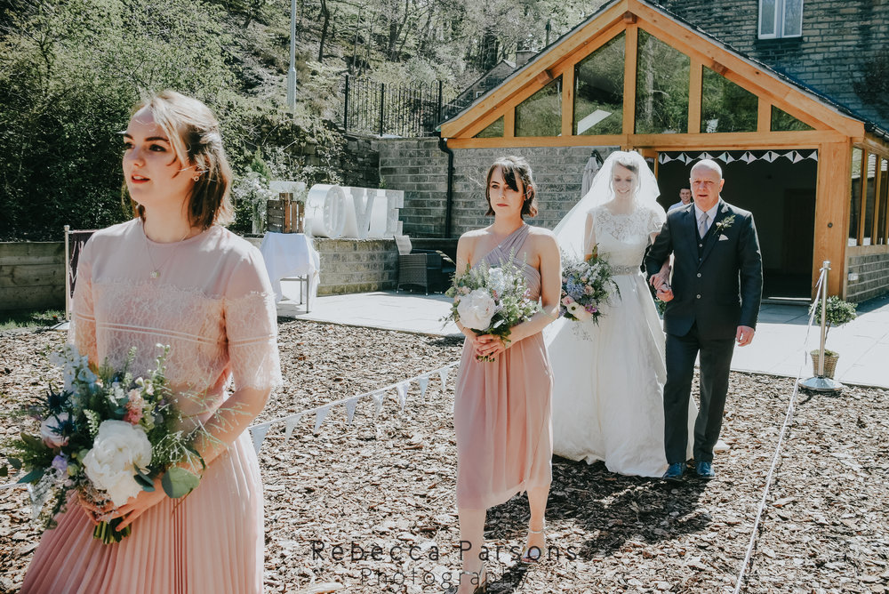 bridal party walking down aisle outdoors