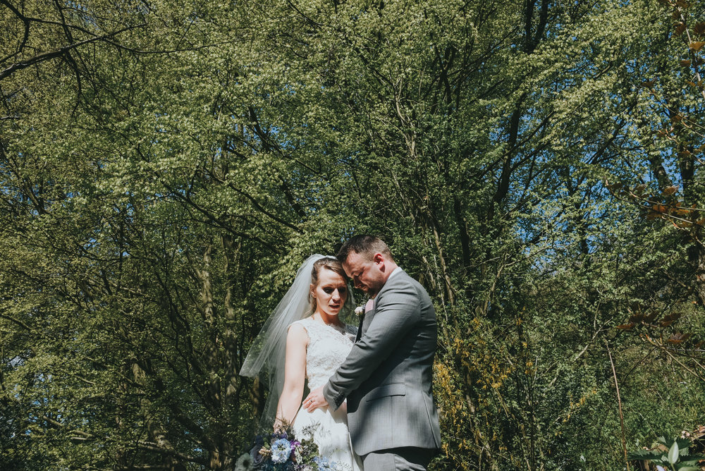 bride and groom cuddling in woodland