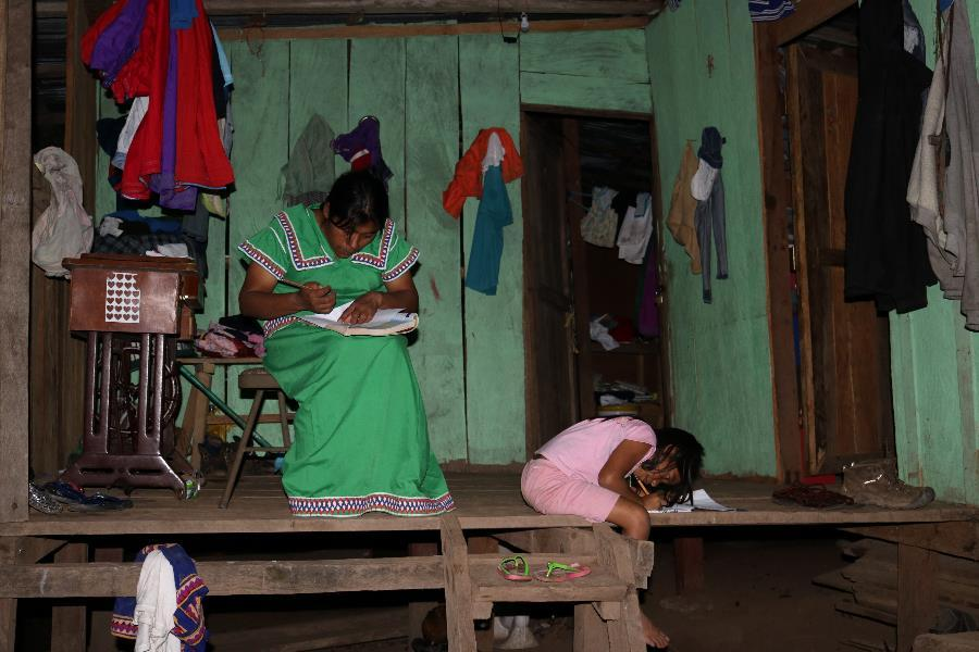 Agripina and her daughter use the last natural light of the day to finish their homework.