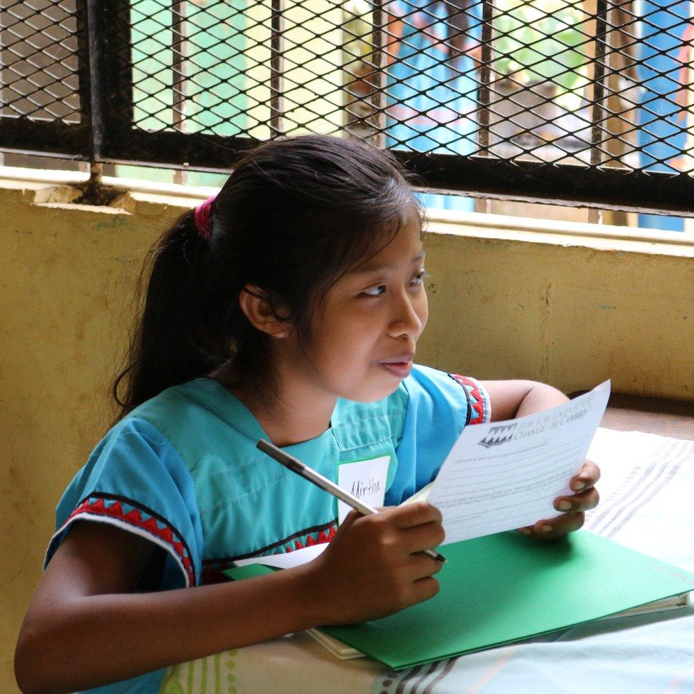 Mirtha working thoughtfully.