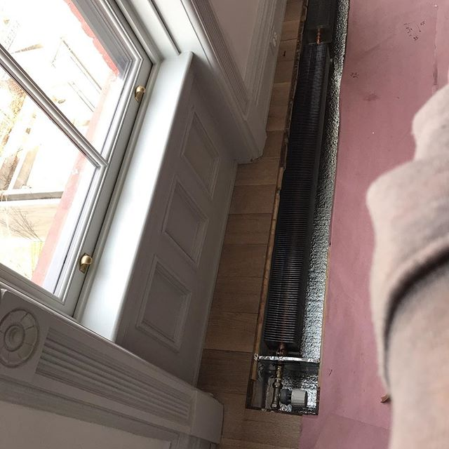 Work in progress- solving heating issues. Original contractor installed in-floor heating units that were too small to provide adequate heat to the space, had no proper control, and no space for convection. Check out the before picture of the radiator as well as the size of the old grills compared to the new radiators, new box, and trvs for control.