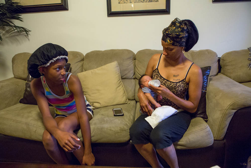 Kim Parker with her daughter (left) holds Desmond's baby. She moved back to New Orleans to care for the baby after being evicted for drug possession. They all live in a market-rate apartment in east New Orleans. Photo by Elaisha Stokes